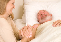 Volunteer Talking with Smilinlg Patient in Bed
